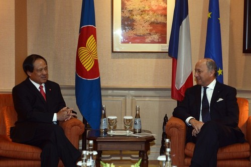 France's foreign minister Laurant Fabius sits across some flags from the ASEAN Secretary Genera, H.E. Le Luong Minh.