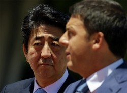 Japanese Prime Minister Shinzo Abe, background, arrives in Rome's Villa Pamphili for a meeting with Italian Premier Matteo Renzi, on June 6, 2014. (AP Photo/Gregorio Borgia)